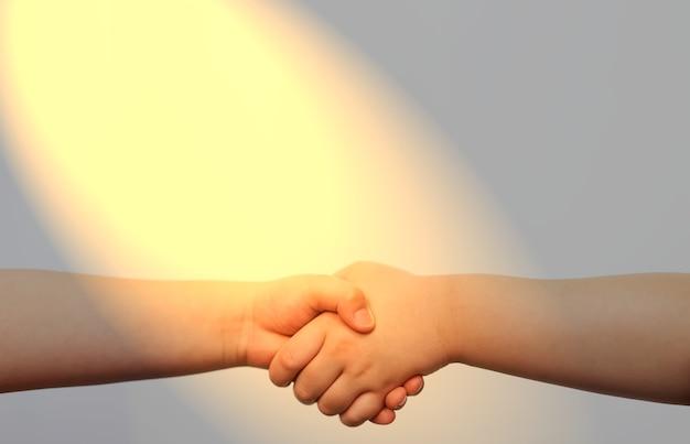 Kid hand shake w początkowej koncepcji partnerstwa ze światłem słonecznym