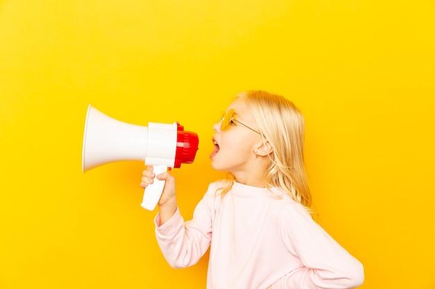 Kid krzyczy przez megafon. koncepcja komunikacji. żółte tło jako kopia o wpisanie tekstu.