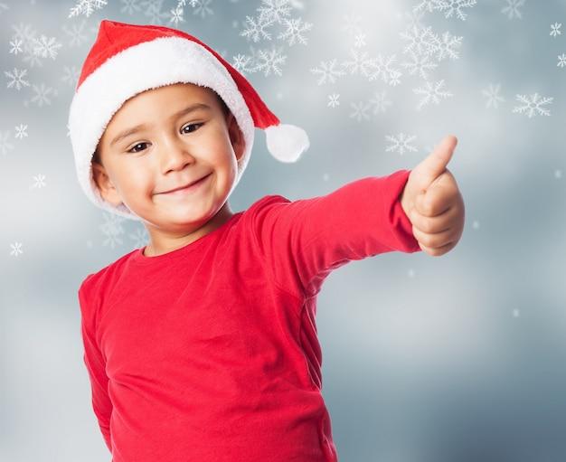Kid z kciukiem do góry i śnieg tle