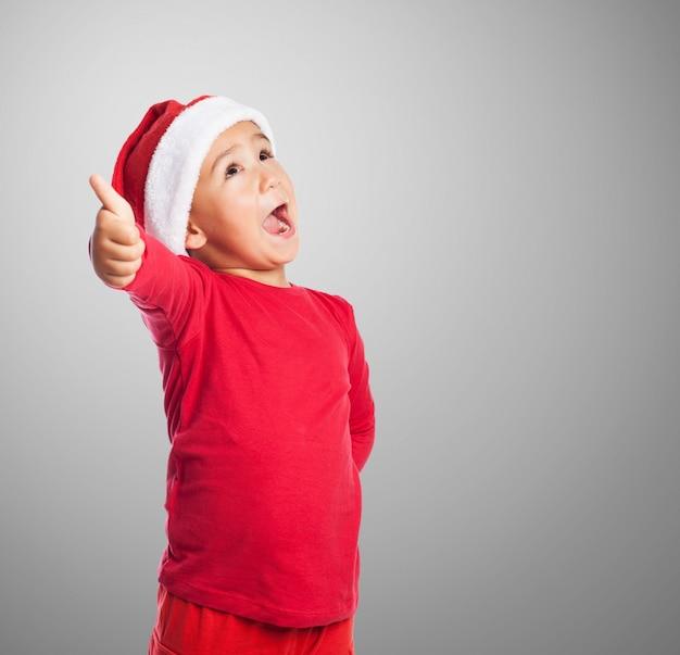 Kid z otwartymi ustami i kciukiem do góry