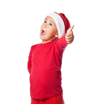 Kid z otwartymi ustami, mikołaj kapelusz i kciuk w górę