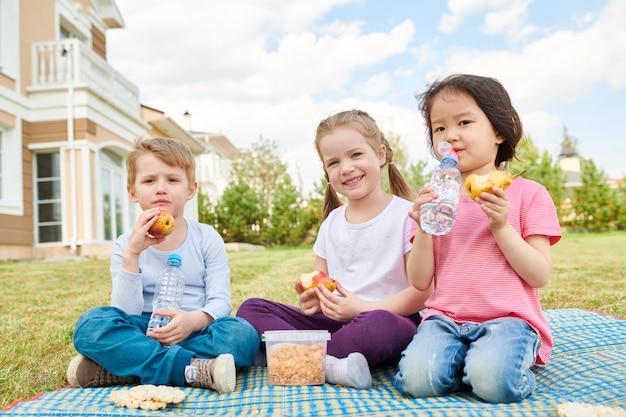 Kids enjoying picnic on lawn