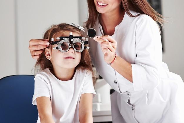 Kiedy praca sprawia, że się uśmiechasz. lekarz sprawdzający wzrok małej dziewczynki i dostrajający foropter.