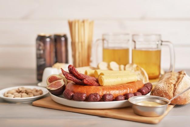 Kiełbasa i plastry sera z lekkim piwem i pistacjami na oktoberfest