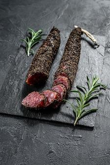 Kiełbasa kiełbasowa. kiełbasa wieprzowa. włoskie antipasto. czarna ściana. widok z góry