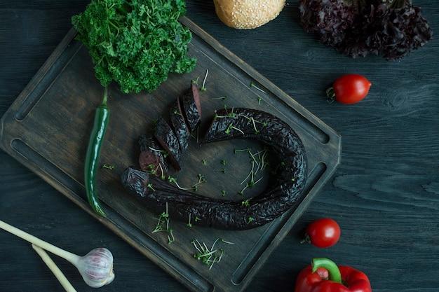 Kiełbasa na ciemnej desce do krojenia jest ozdobiona świeżymi ziołami i warzywami. kaszanka