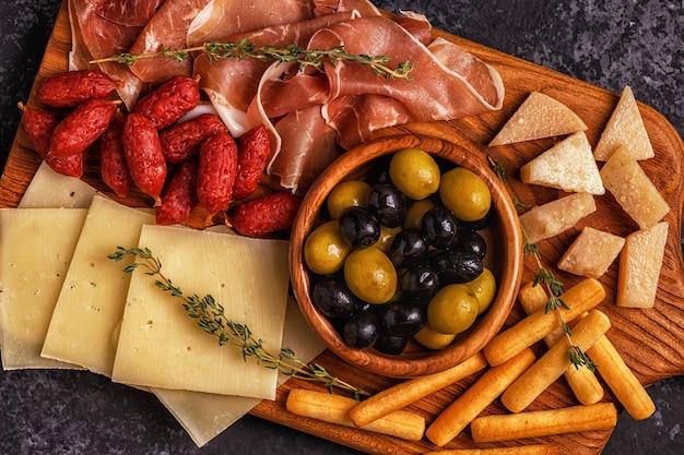Kiełbasa oliwki ser prosciutto paluszki chlebowe wino