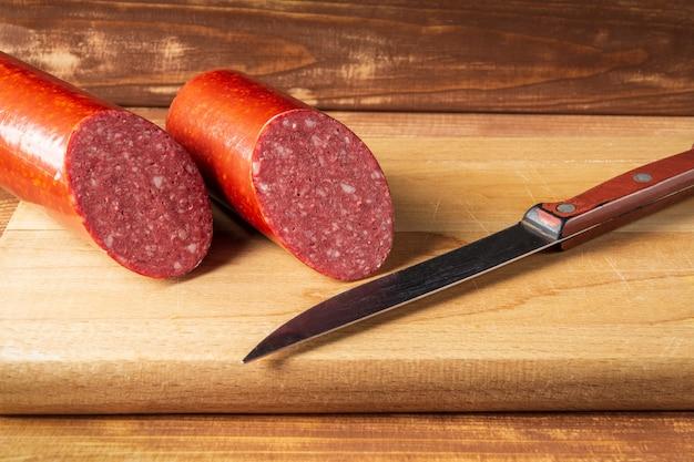 Kiełbasa salami w plasterkach i nóż na desce do krojenia pomysł na przygotowanie żywności