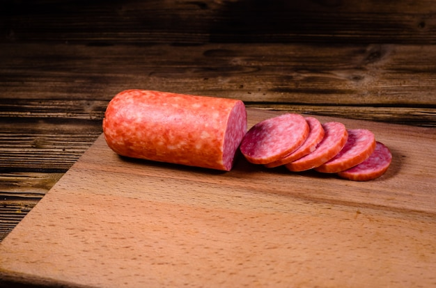 Kiełbasa salami w plasterkach na desce do krojenia
