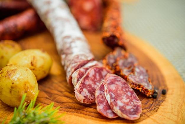 Kiełbasa salami z oszkloną cebulą na drewnianej desce do krojenia.