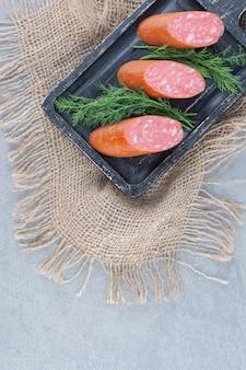 Kiełbasa salami z plastrami na czarnym talerzu.