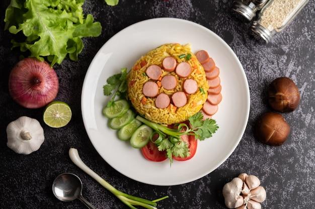 Kiełbasa smażony ryż z pomidorami, marchewką i grzybami shiitake na talerzu