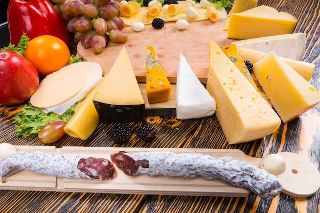 Kiełbasa suszona na ostro i półmisek serów z układem wielu różnych serów na stole bufetowym podczas imprezy cateringowej lub przyjęcia