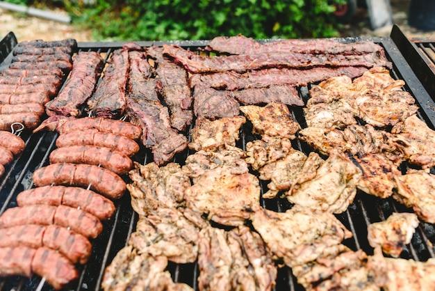 Kiełbasa, wieprzowina i kurczak pieczone na grillu, widziane z góry.