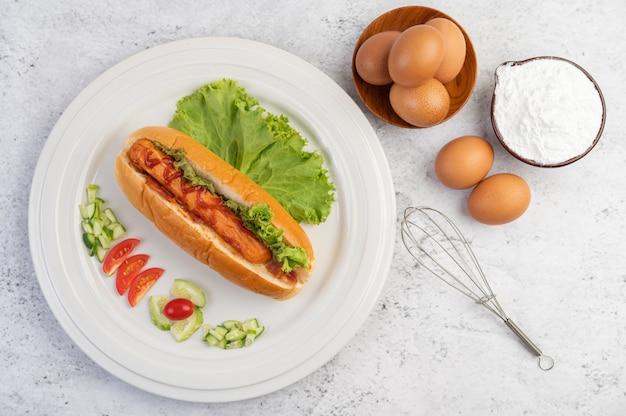 Kiełbasa zawijana w chleb i sałatę z sosem.