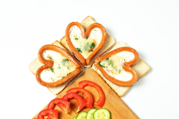 Kiełbaski w formie serca, na próbach, z siekanymi warzywami, odizolowane, widok z góry