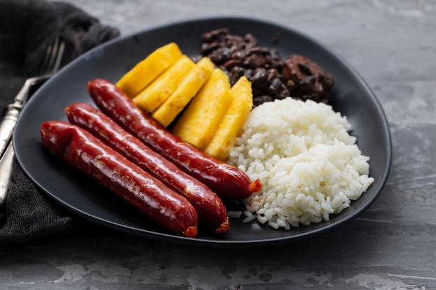 Kiełbaski z ryżem, czarną fasolą i ananasem na ciemnym talerzu