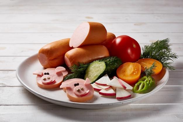 Kiełbaski z warzywami i ziołami udekorowane sosami i chlebem na szarym talerzu ceramicznym na białym drewnianym stole.