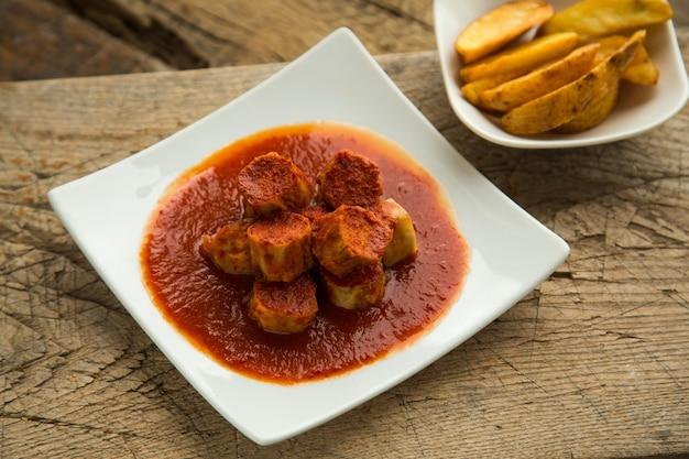 Kiełbasy curry z kurczaka podawane na talerzu ze specjalnym sosem. grillowane kiełbaski bawarskie z przyprawami indyjskimi.