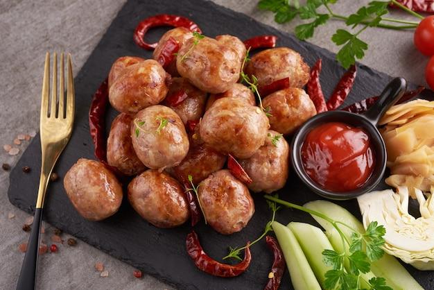 Kiełbasy domowej roboty z tajskimi ziołami, warzywami. domowe kiełbaski z mięsa wieprzowego w skórkach z dodatkiem ziół i przypraw. widok z góry.