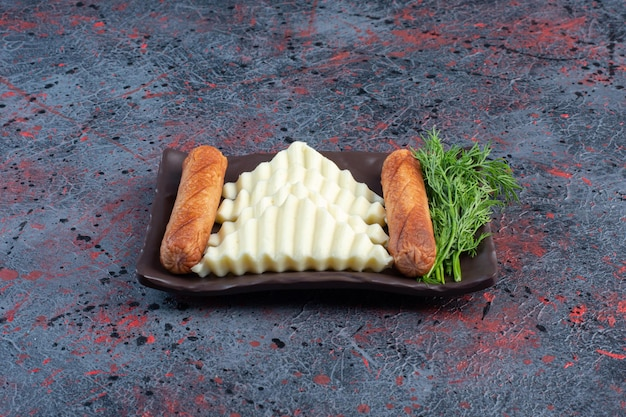 Kiełbasy grillowane z plastrami białego sera.