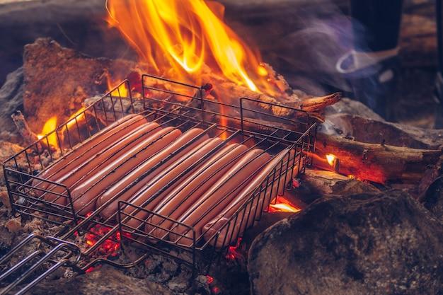 Kiełbasy grilluje się na ogniu. kemping na wsi. na świeżym powietrzu styl życia z grilla, gotowanie pysznego posiłku