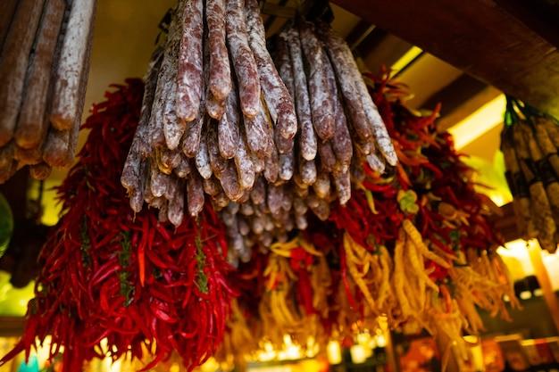 Kiełbasy i papryki wiszące na tradycyjnym wiejskim targu