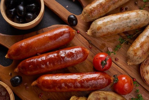 Kiełbasy i składniki do gotowania. kiełbasa z grilla z dodatkiem ziół i przypraw