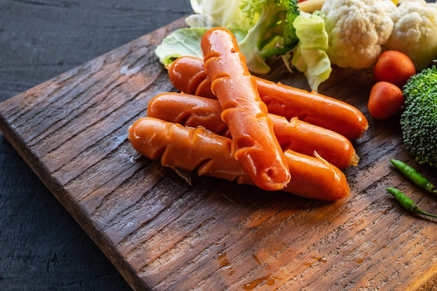 Kiełbasy i warzywa na drewnianej desce do krojenia