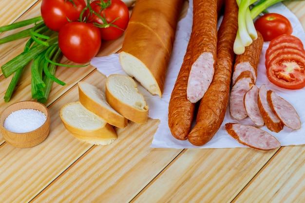 Kiełbasy krakowskie na papierze z dodatkiem warzyw i soli.