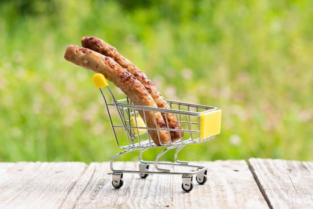 Kiełbasy mięsne są w małym wózku do smażenia na ogniu.