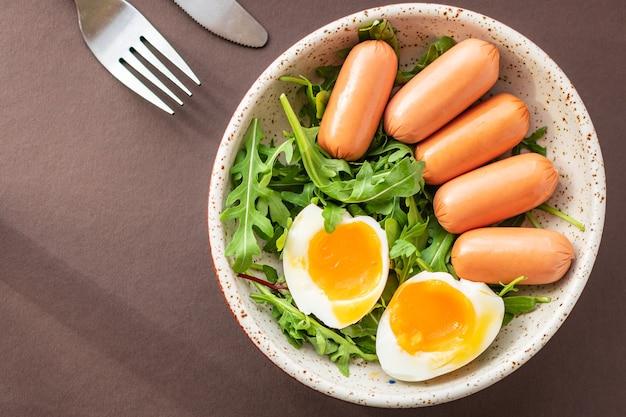 Kiełbasy sałatka jajko gotowane liście zielone płatki sałata mix świeża zdrowo