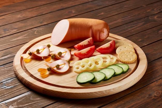 Kiełbasy z dodatkami warzyw i ziół z sosami i chlebem na drewnianym talerzu na ciemnym drewnianym stole.