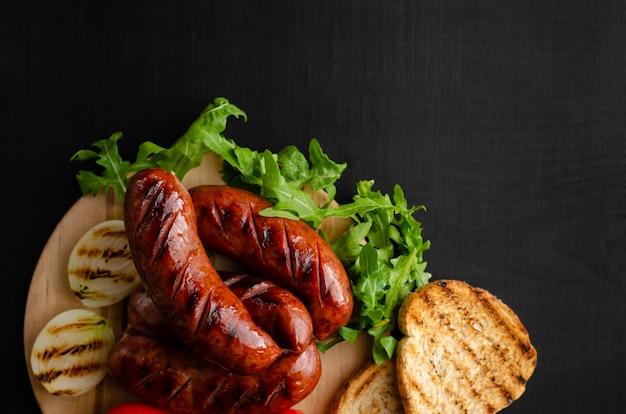 Kiełbasy z grilla, chleb tostowy, cebula i świeża rukola na czarnym tle. , leżał płasko