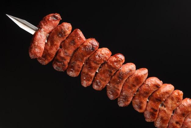 Kiełbasy z grilla na szaszłykach na czarnym tle.