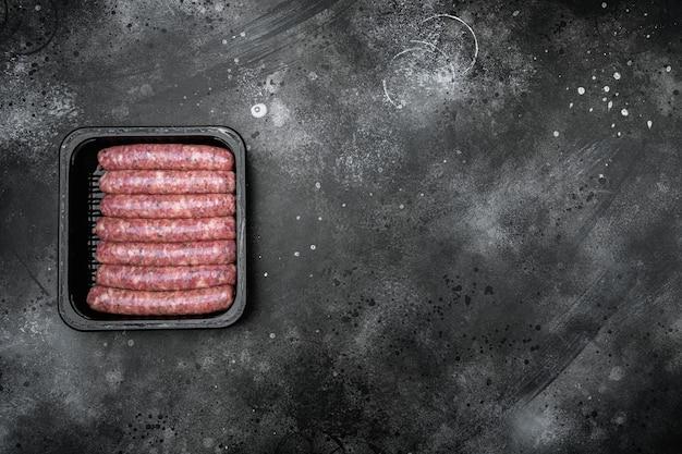 Kiełbasy z surowego mięsa w zestawie do pakowania, na czarnym ciemnym tle kamiennego stołu, widok z góry na płasko, z miejscem na kopię na tekst