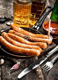 Kiełbasy z zimnym piwem i sosem na drewnianym stole.