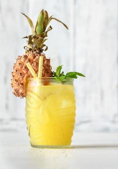 Kieliszek ananasowy koktajl w stylu tiki na białym tle