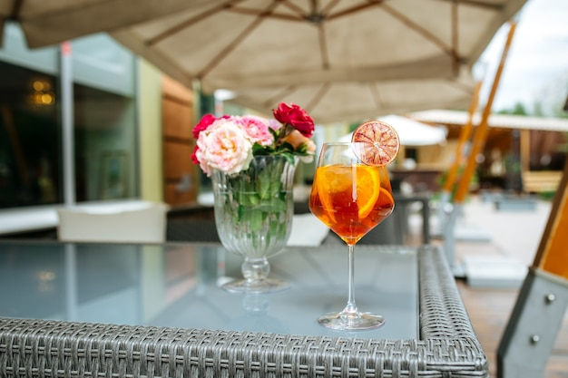 Kieliszek aperole spritz koktajl przyozdobiony plasterkiem pomarańczy na stole z kwiatami