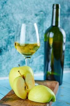 Kieliszek białego wina i butelka z plasterkami jabłka na niebieskiej ścianie.