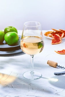 Kieliszek białego wina i talerz zielonych jabłek
