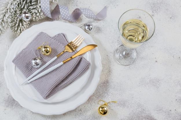 Kieliszek białego wina musującego lub szampana i nowy rok dekoracji na jasnym tle. koncepcja ferii zimowych. widok z góry