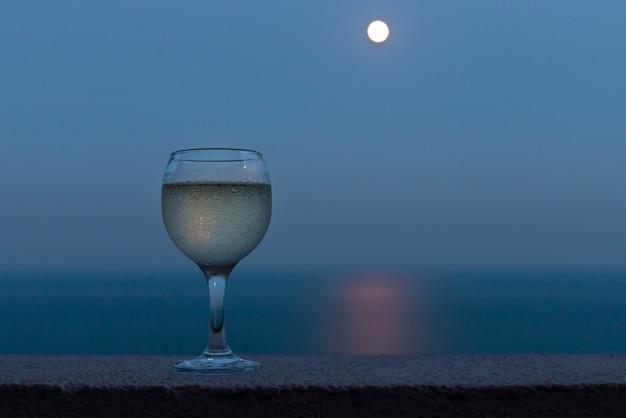 Kieliszek białego wina na balkonie z niewyraźnym morzem i księżycem w pełni