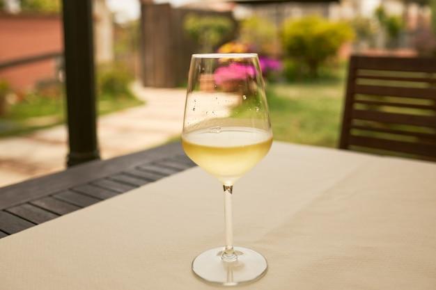 Kieliszek białego wina na stole na tarasie.