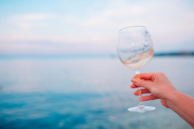Kieliszek białego wina na tropikalnej plaży