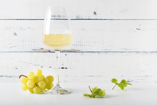 Kieliszek białego wina na vintage drewniany stół