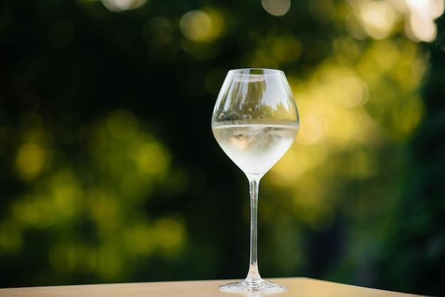 Kieliszek białego wina na zewnątrz o zachodzie słońca. wyśmienite białe wino w kieliszku