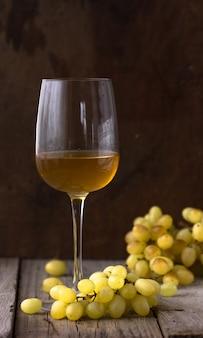 Kieliszek białego wina w piwnicy. stare białe wino na drewnie.