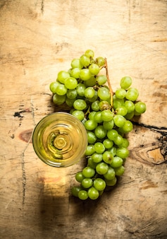 Kieliszek białego wina z gałęzi dojrzałych winogron na drewnianym stole.