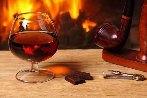 Kieliszek brandy, czekolady i fajki tytoniowej na dębowym stole na tle płonącego kominka
